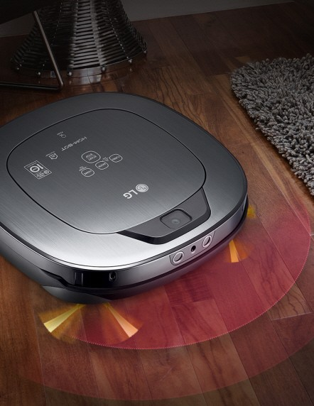 LG HOM-BOT Turbo+ navigating across a hard wood floor and obstacles such as a living room carpet, a decorative piece and a chair leg.