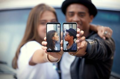 A young couple each hold the LG Q6 in their holds, each displaying a picture of themselves giving air kisses