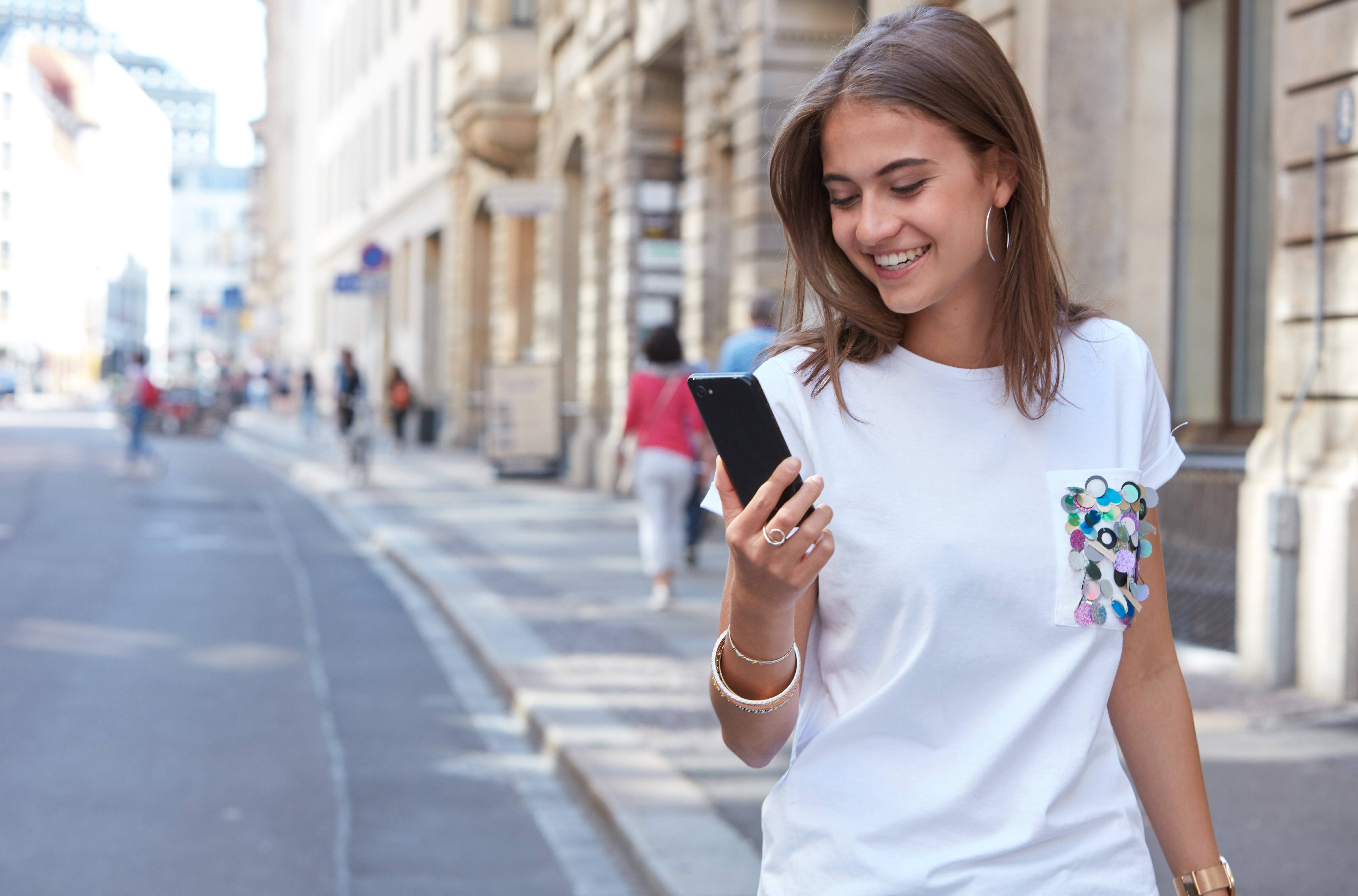 A woman walking down the street while looking at the LG G6 in her hand