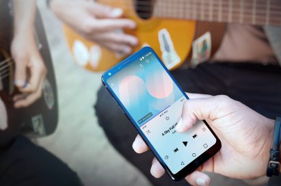 A person playing a song on the LG G6 via speakers