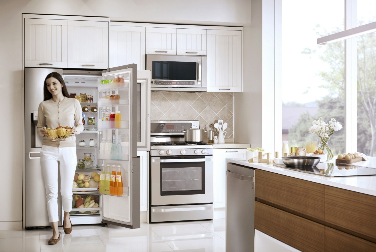 Woman taking a basket of fruit out of the LG InstaView Door-In-Door™ refrigerator's main compartment