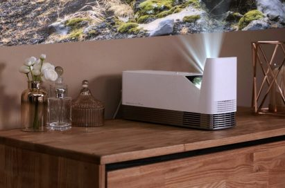 The LG ProBeam Projector model HF85J placed on top of living room furniture