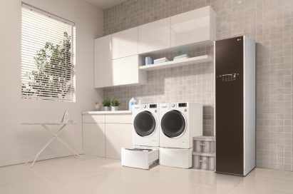 LG Styler and one LG washing machine with the TWINWash™ Mini unit open next to LG dryer with the pedestal unit closed in a laundry room with tiled walls