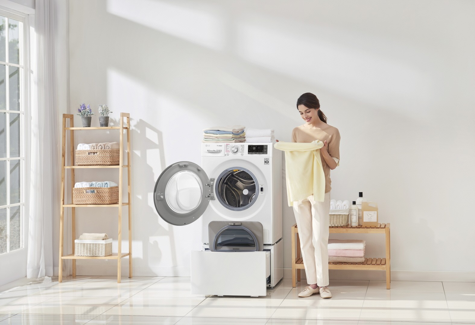 A woman holding yellow towel and standing next to LG TWINWash™ washing machine with both doors open and folded towels stacked on top of the washer in a laundry room