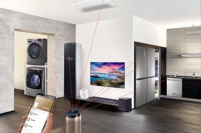 Hand holding smartphone in an apartment with lines connecting an LG ThinQ Hub speaker to a washing machine, dryer, Styler, refrigerator, dishwasher, air conditioner and air purifier