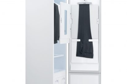 Side view of LG Styler with its door open, showing trousers hanging on the door and a jacket and white shirt hanging inside