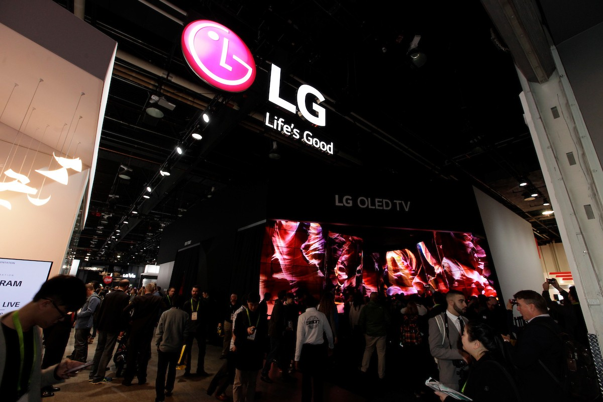 LG's booth at CES 2018 with visitors in the foreground, the logo and 'Life's Good' slogan above, and an LG OLED TV sign in the background