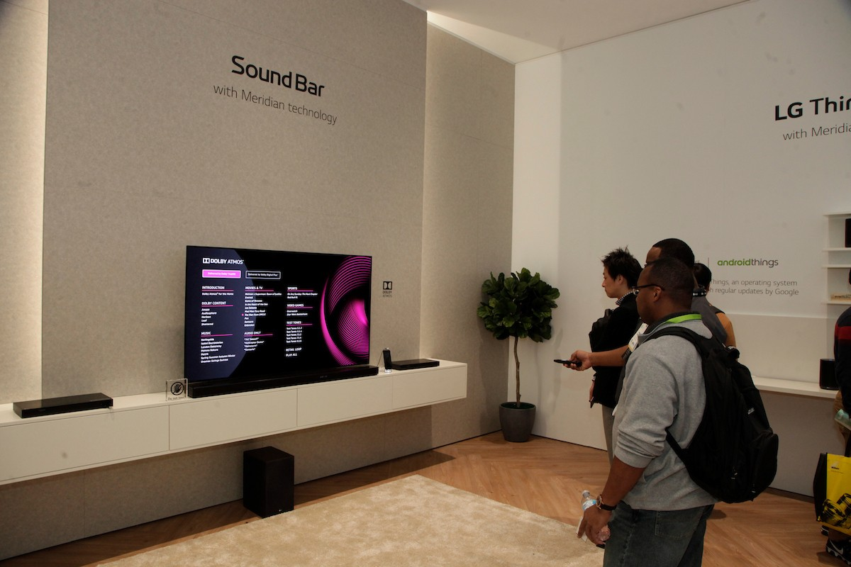 Visitors listen to audio on an LG sound bar connected to an LG TV in the CES LG Sound Bar highlight zone