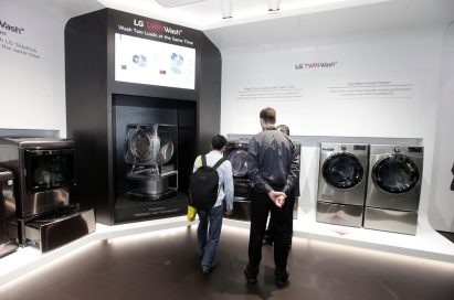 Visitors and an LG representative explore the LG TWINWash zone at CES 2018 together.