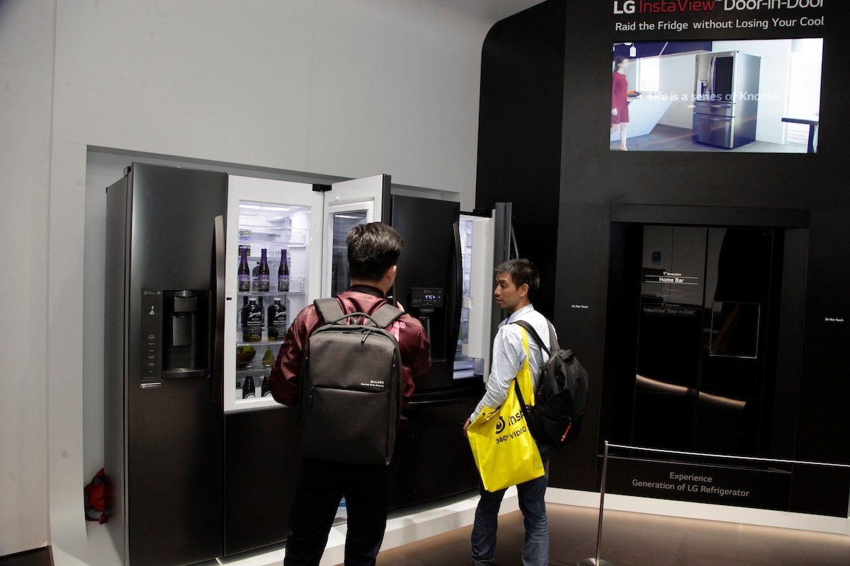 Two visitors open the LG InstaView Door-in-Door refrigerators on display at LG's Home Appliance zone at CES 2018, while discussing its InstaView feature.