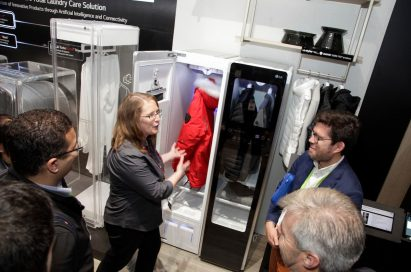 A woman explains LG Styler's sanitizing capabilities to visitors of LG's CES 2018 booth.