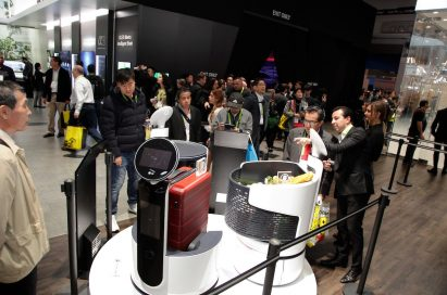 Visitors to LG's CES 2018 take a closer look at the LG CLOi commercial robot lineup, with the ServeBot, PorterBot and CartBot all on display.