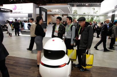 A woman explains and demonstrates the LG CLOi GuideBot to three CES 2018 visitors at the LG booth