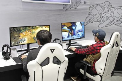 Two visitors sit on gaming chairs while playing games on LG's 21:9 UltraWide Gaming monitors.