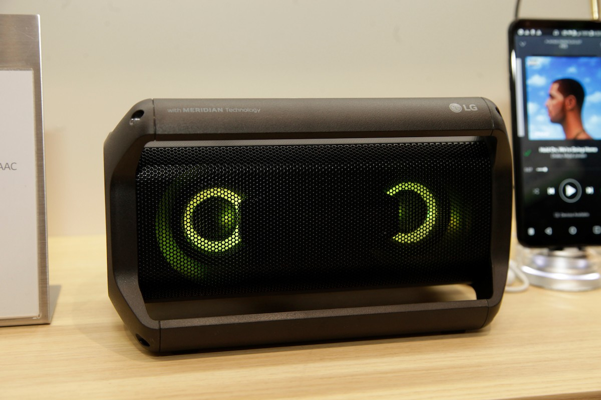Front view of LG's Portable Speaker placed next to the company's smartphone