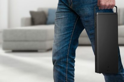 A man carrying the highly portable LG 4K UHD Projector in one hand