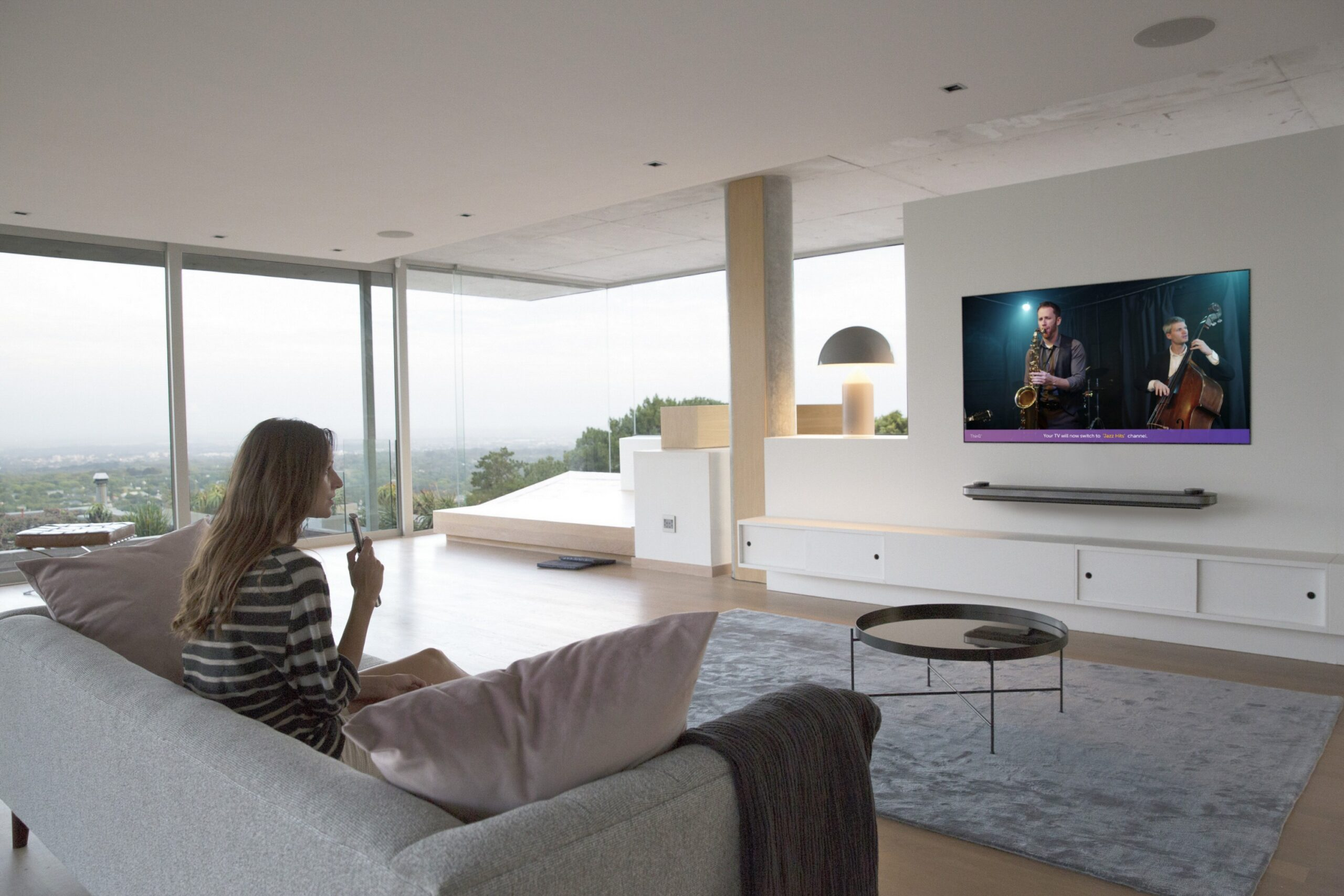A woman sitting on a couch in a modern apartment watching a jazz band play on her LG AI OLED TV