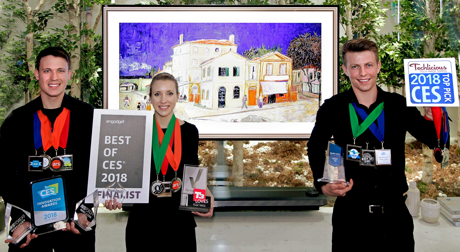 Models pose with the awards from Engadget, T3, Techlicious and more after LG won Best TV product honors at CES 2018.