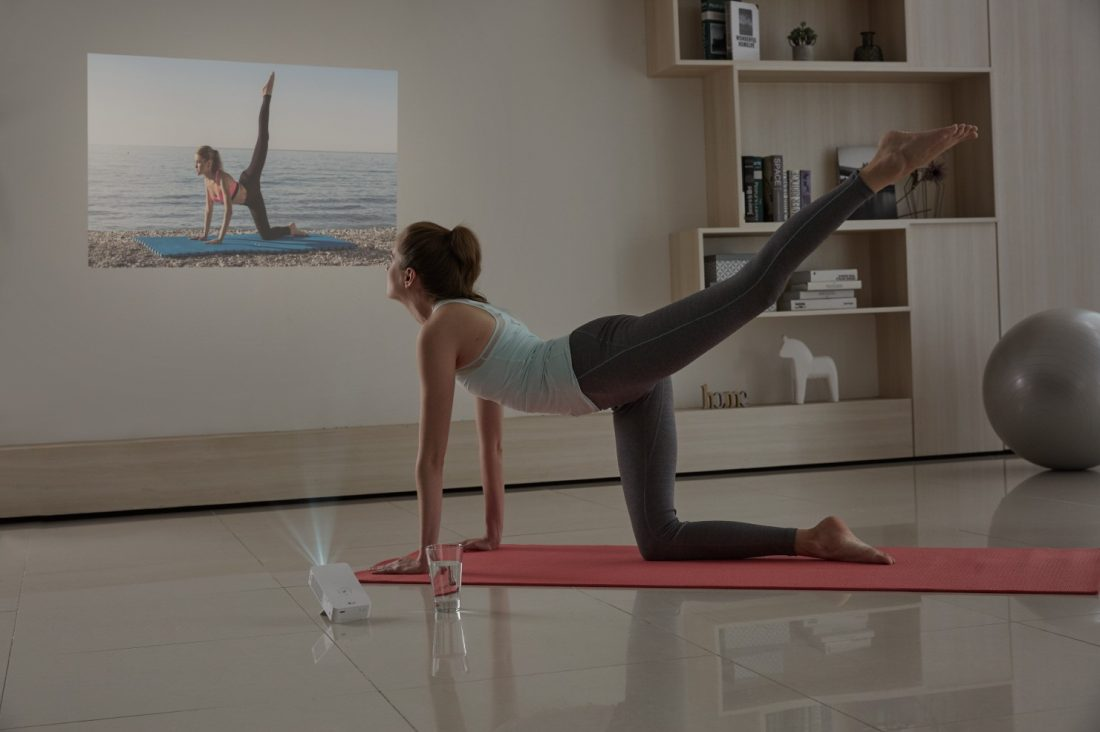 A woman doing yoga while watching a projection from the LG MiniBeam Projector