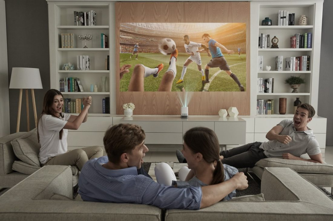 Four people sitting on couches enjoy watching a soccer game projected on the wall by the LG ProBeam Projector HF85J.
