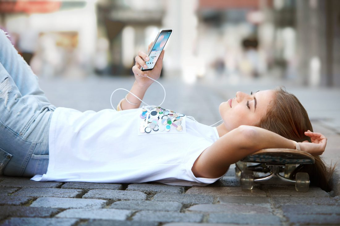 A woman lies on the ground with her skateboard while listening to music on headphones on her LG Q6