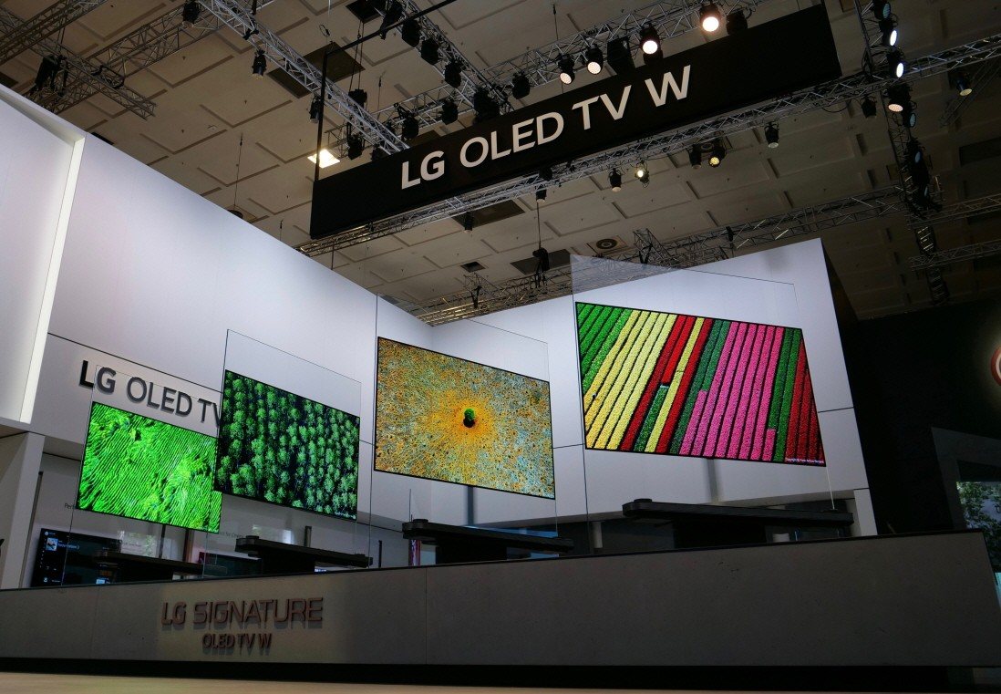 Four LG SIGNATURE OLED TV W sets placed side by side on a display stand rotate simultaneously.