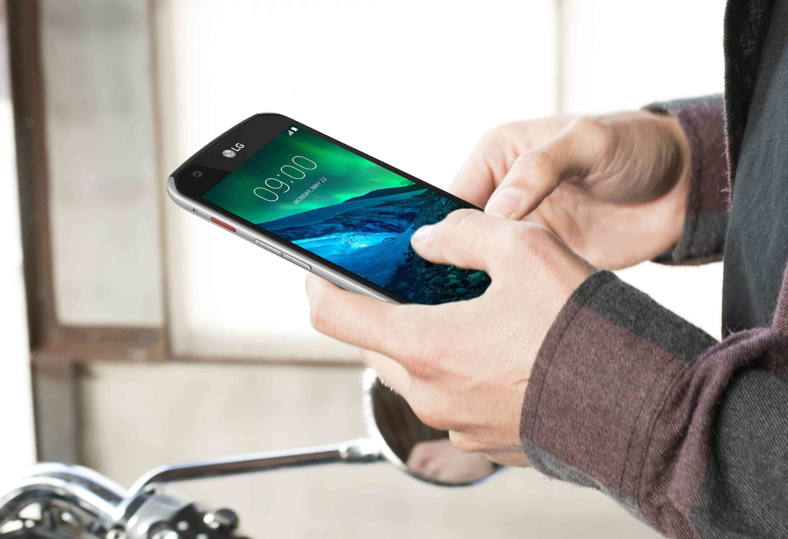 Close-up view of a pair of hands holding the LG X Venture smartphone