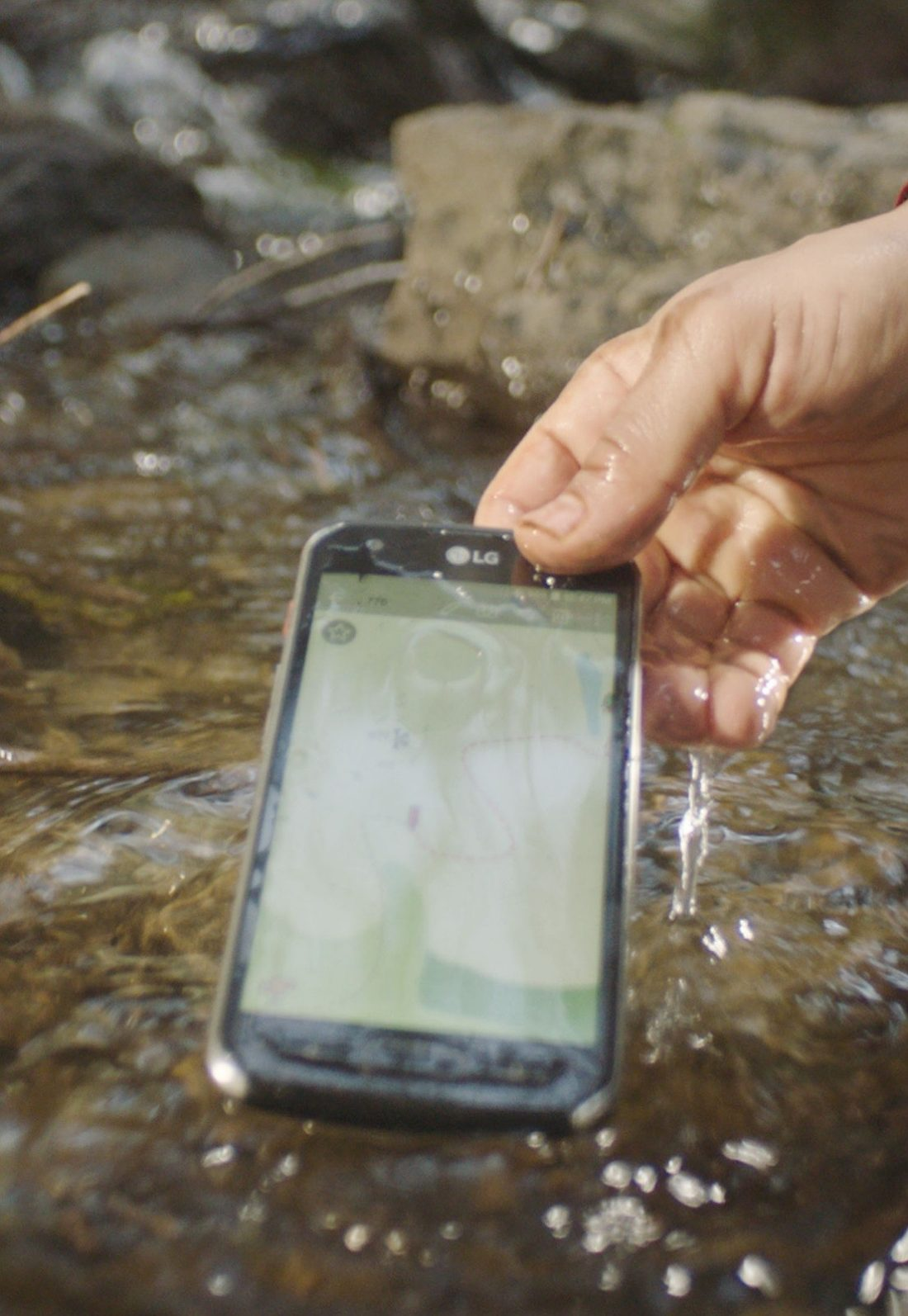 A hand lifting the water-resistant LG X Venture smartphone from water, the phone is still turned on