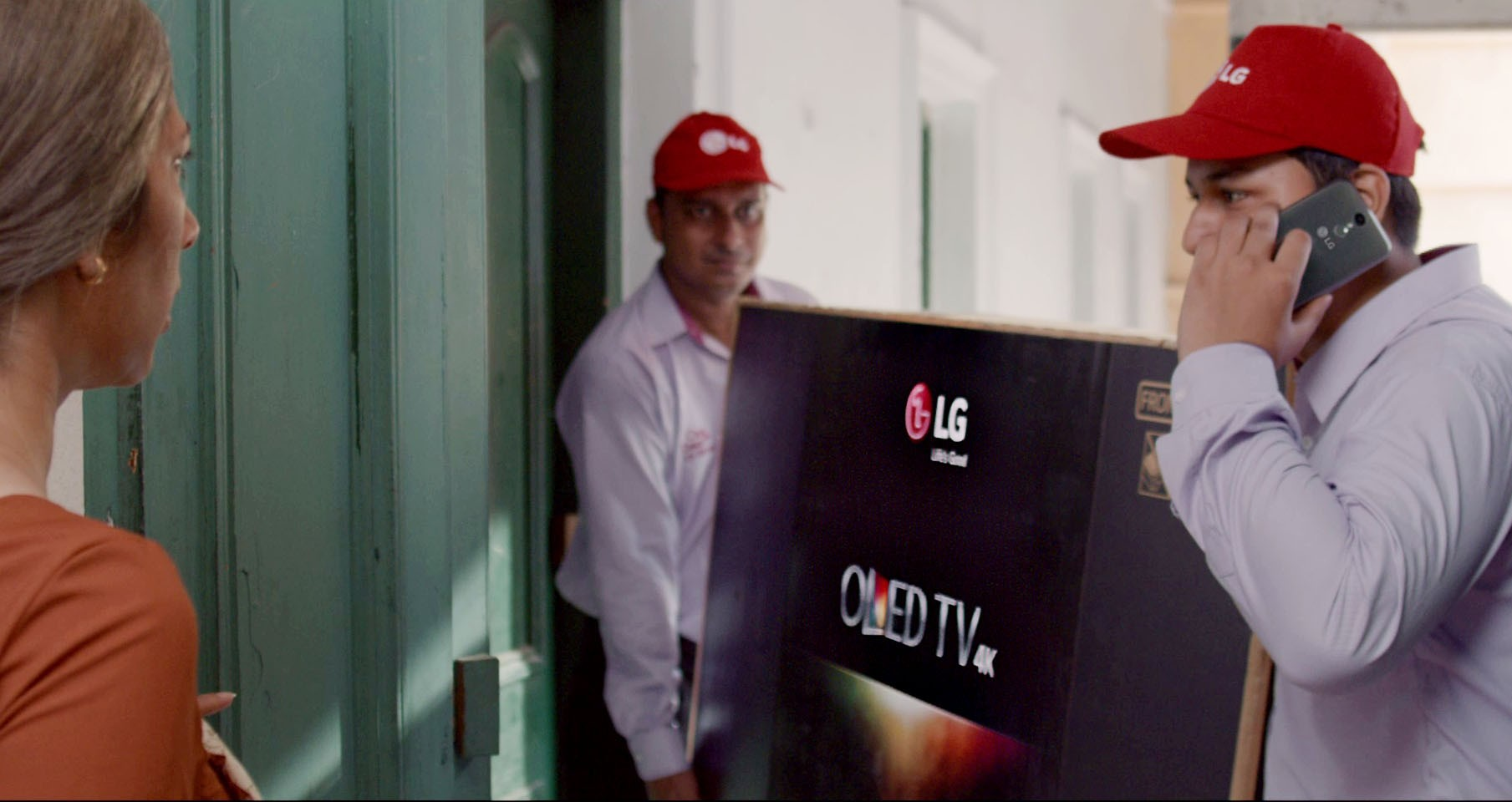 """A screenshot of LG India's """"Astronaut"""" video, two men are delivering LG OLED TV to a woman's house."""