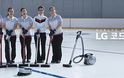 """South Korea's women curlers, known as """"Team Kim"""" stands abreast with LG CordZero vacuum cleaners in front."""