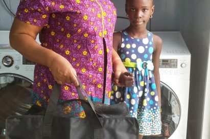 A woman stands with a little girl and smiles with LG's gift bag in front of LG's washing machine.