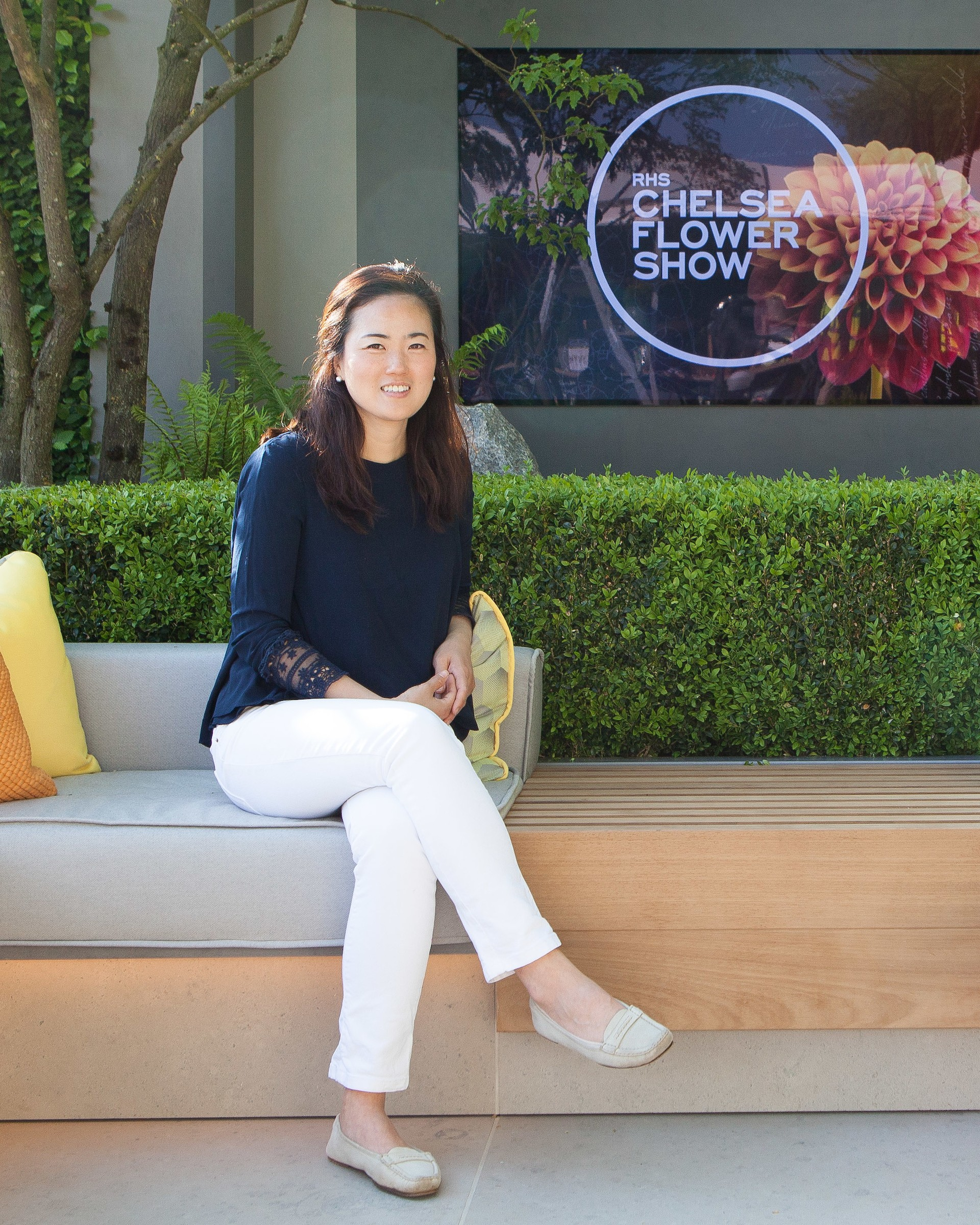 Korean landscape architect Hwang Hay-joung sits on a couch in front of the RHS Chelsea Flower Show logo.