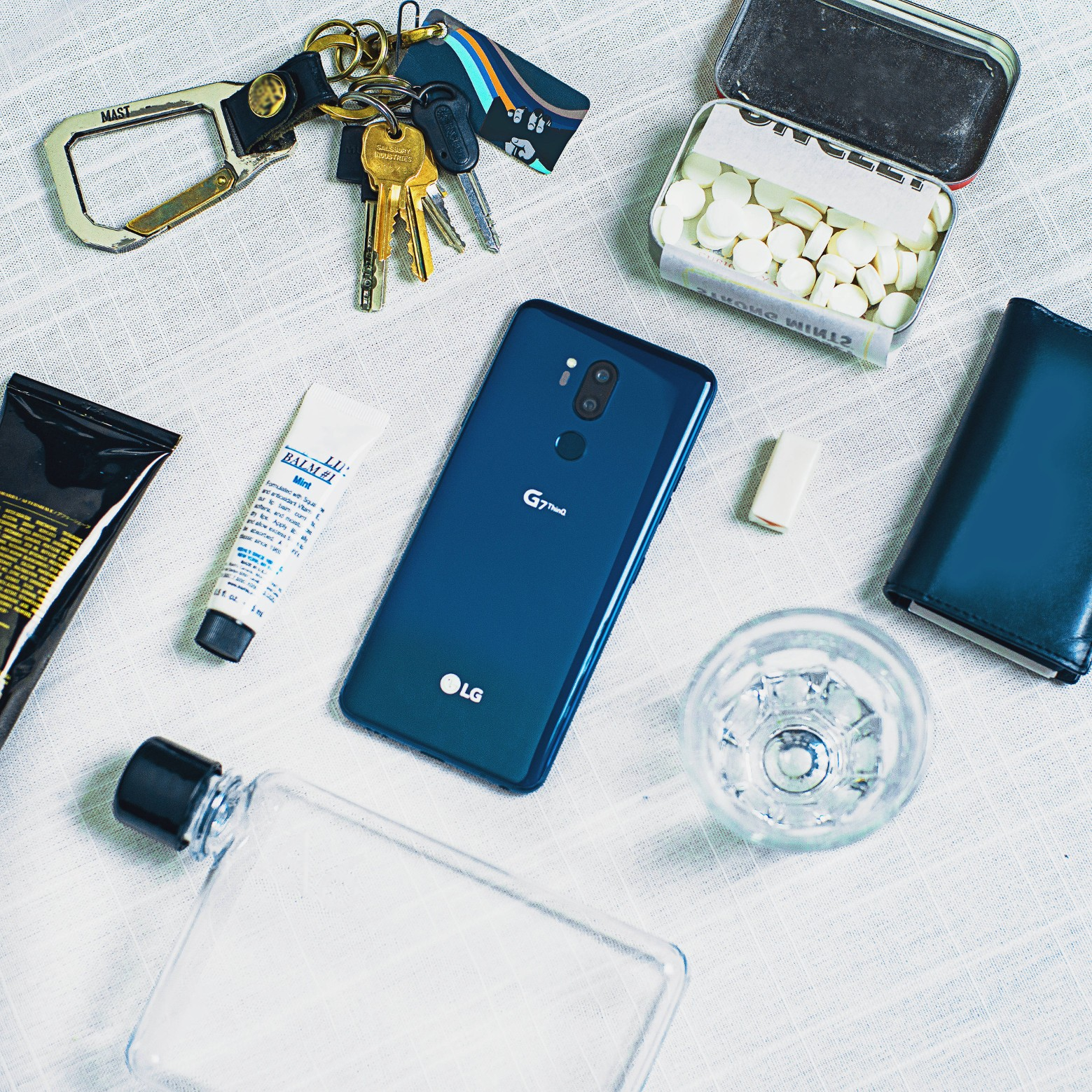 The LG G7 ThinQ in New Moroccan Blue face down on a table, next to other lifestyle items, such as keys, a water bottle, mints, etc.