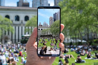 A person holding the LG G7 ThinQ and taking a picture of crowded park in the city