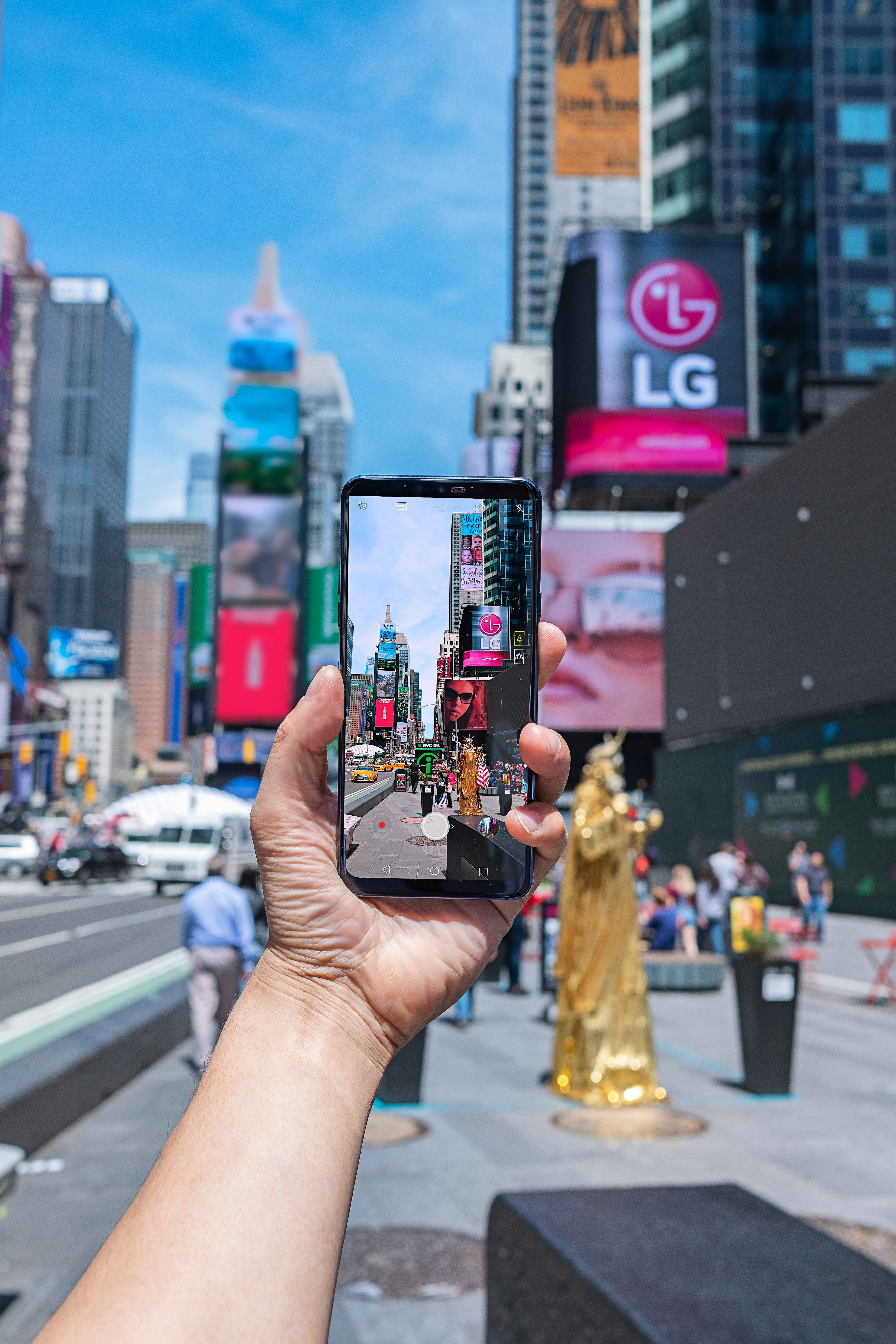 A person taking a photo of Times Square in New York with AI CAM on the LG G7 ThinQ