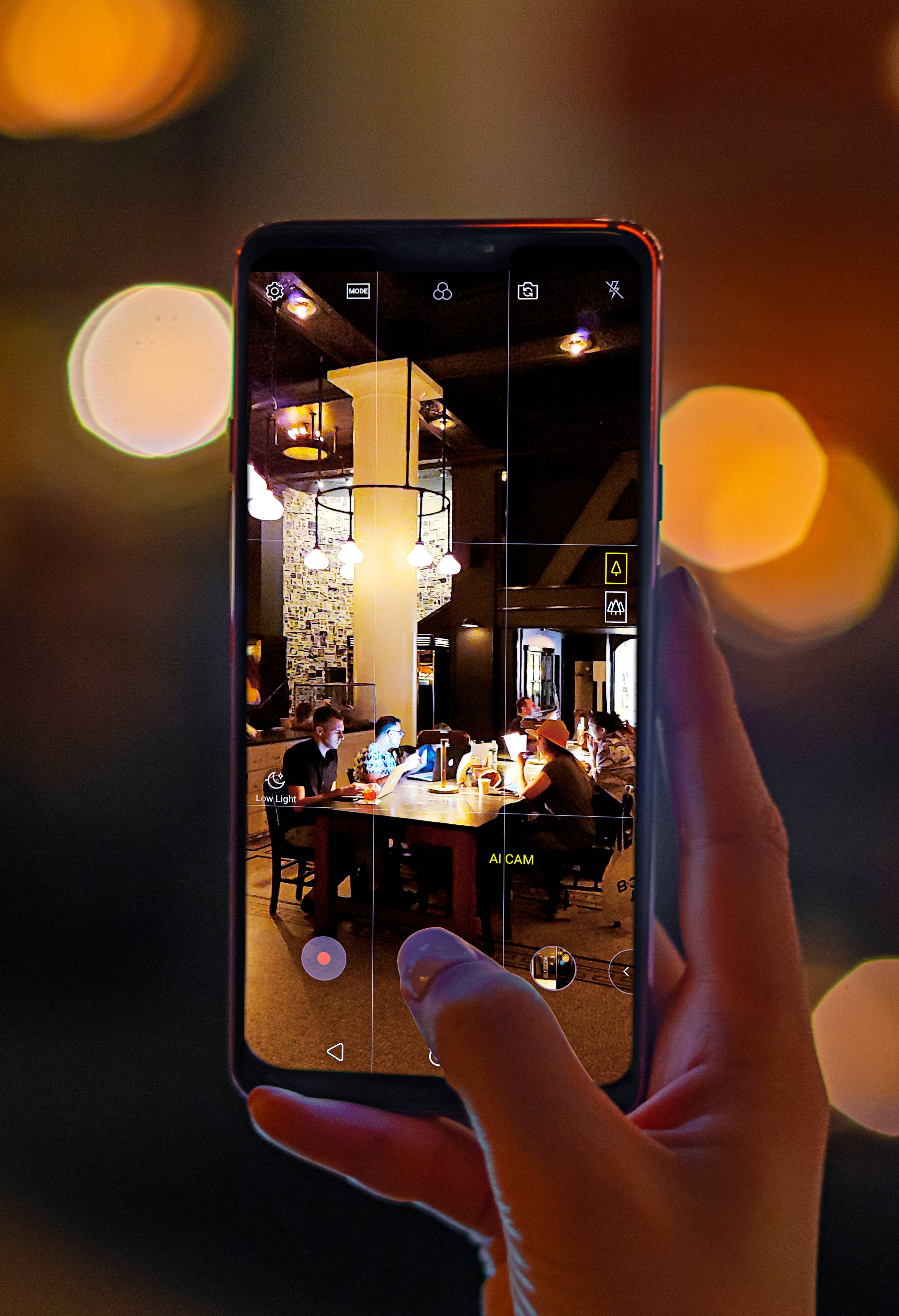 A person taking a photo of a dark cafe with AI CAM on the LG G7 ThinQ