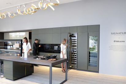 Woman trying cooktop, man trying wall oven and woman opening wine cellar at SIGNATURE KITCHEN SUITE's exhibition hall cooperated with Valcucine at IFA 2018