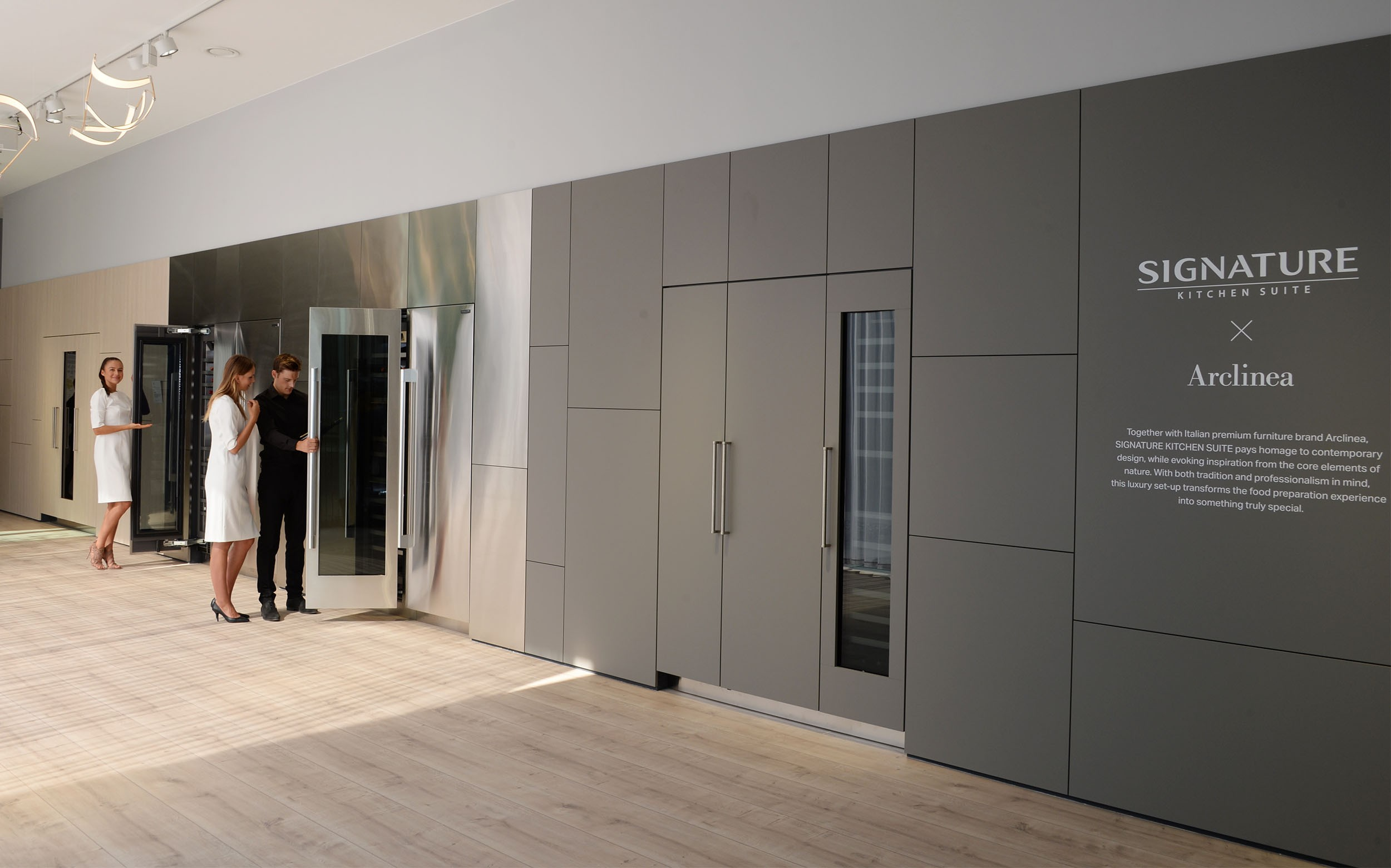 2 women and 1 man viewing wine cellars at SIGNATURE KITCHEN SUITE's exhibition hall cooperated with Arclinea at IFA 2018