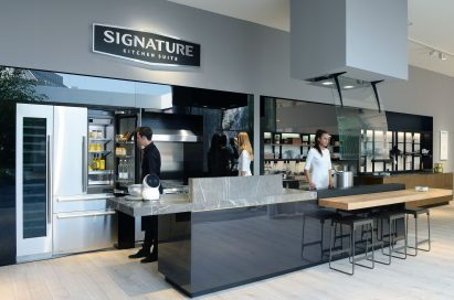 Man opening refrigerator, woman trying cooktop and woman trying wall oven at SIGNATURE KITCHEN SUITE's exhibition hall cooperated with Valcucine at IFA 2018