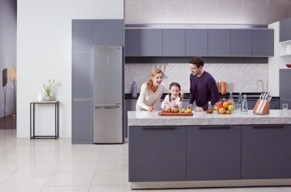 Little girl and her parents cutting fruit on the counter with LG Centum System™ bottom-freezer refrigerator in the background