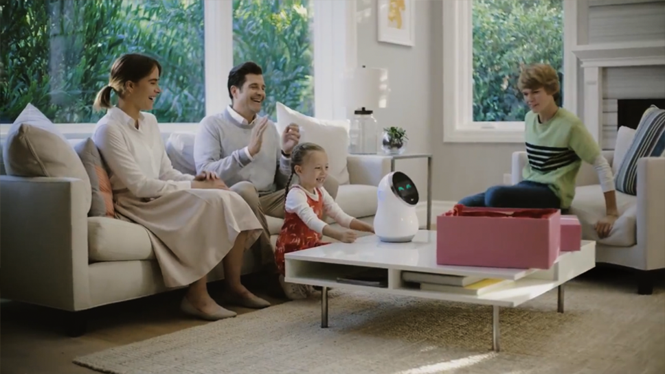 Four members of a family enjoy their time together using LG's CLOi Hub Robot in the living room.