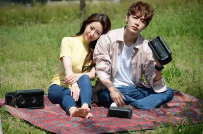 A man and a woman sitting outside on a picnic blanket enjoying music on their LG XBOOMs