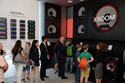 Visitors look at the products of LG XBOOM GO lineup which offers Meridian's premium sound.