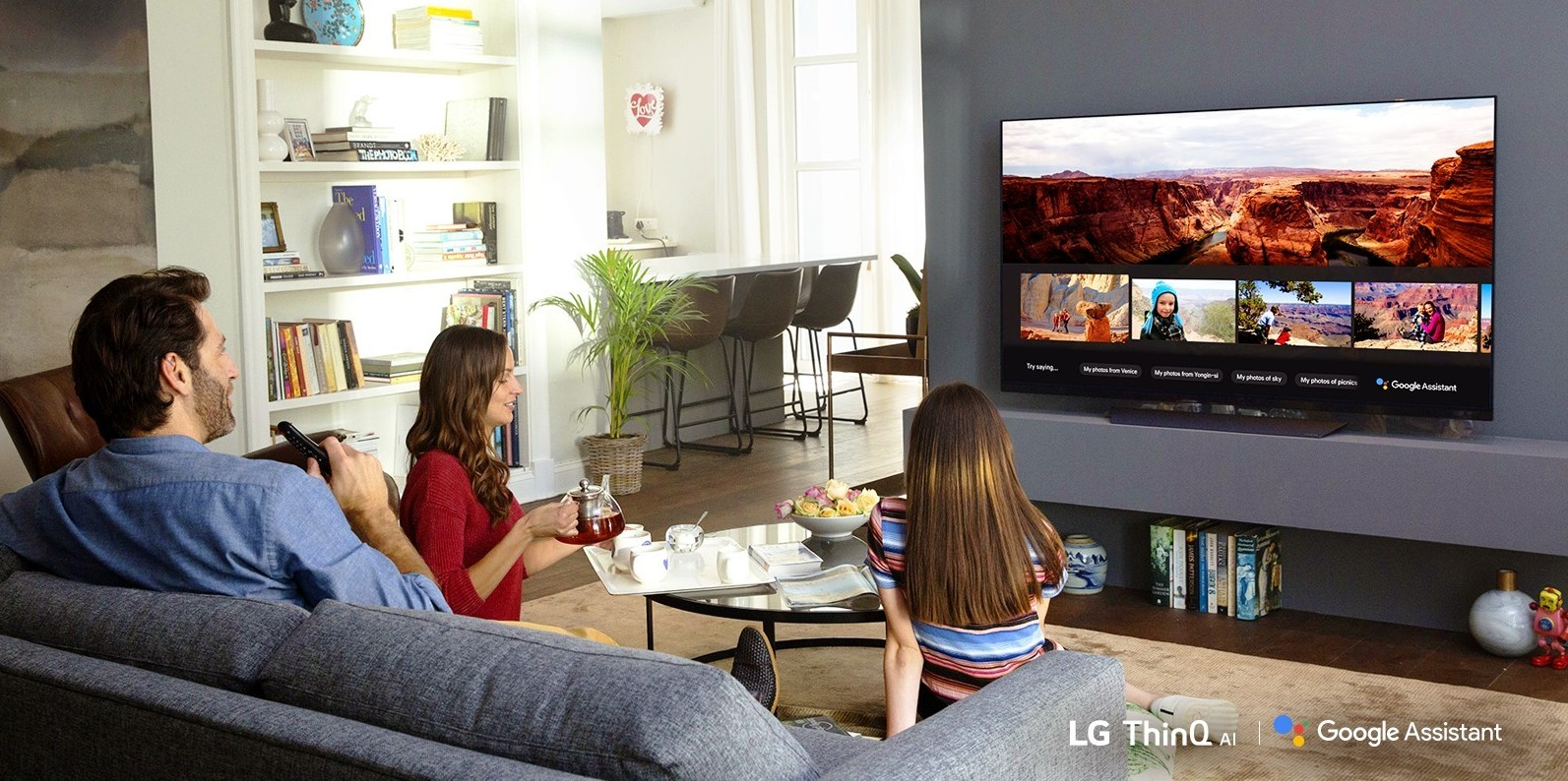 A family sits in the living room while looking at their travel photos via Google Assistant on LG's ThinQ TV.