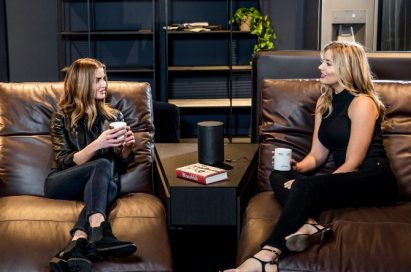 Two women sit on Natuzzi's Colosseo sofa, talking to each other with LG's AI smart speaker placed between them.