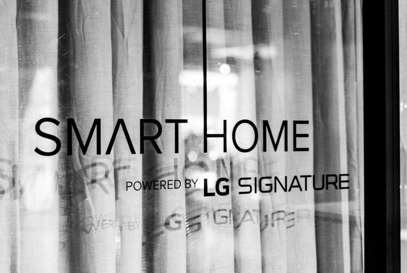 """The logo of the """"Smart Home powered by LG SIGNATURE"""" attached on the glass at the event zone"""