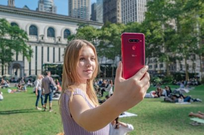 A woman holds up and looks at the display of the LG V40 ThinQ in the Carmine Red color.