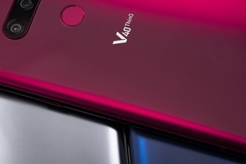 A Carmine Red LG V40 ThinQ is placed on LG V40 ThinQ smartphones in two different colors – New Platinum Grey and New Moroccan Blue.