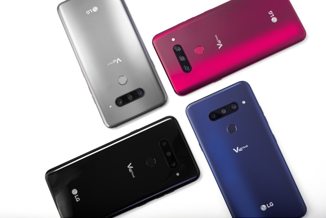 Four LG V40 ThinQ smartphones in New Aurora Black, New Platinum Grey, New Moroccan Blue and Carmine Red are placed in a brick pattern.