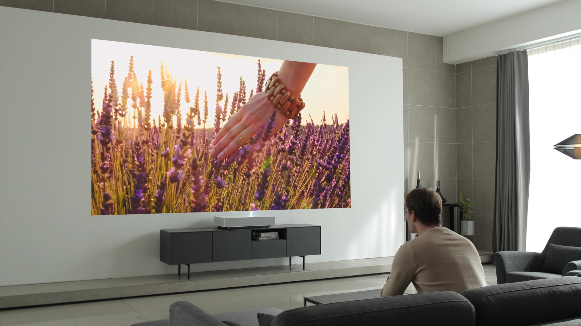 A man is watching a vivid image displayed by the LG CineBeam Laser 4K projector model HU85L